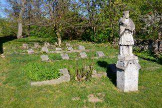 Nepomuki Szent János-szobor és katonai sírok a Szent Anna-templom kertjében