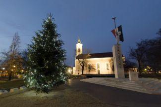 kivilágított karácsonyfa, háttérben a csepeli Kisboldogasszony-templom mellett