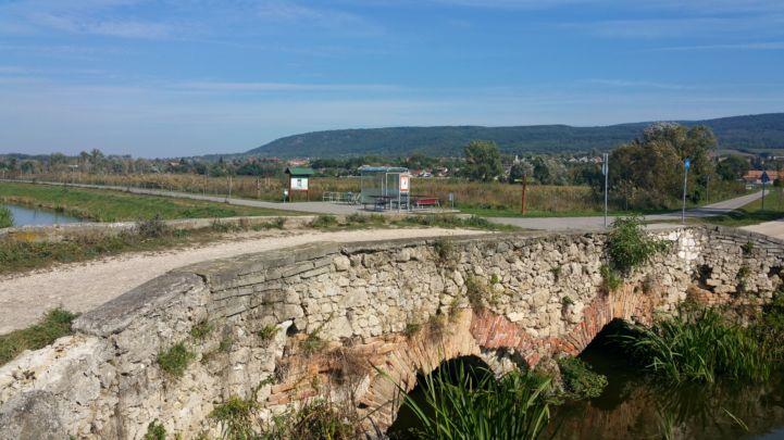 kőhíd az Által-ér völgyi kerékpárút mellett a háttérben egy pihenőhellyel