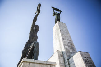 Szabadság-szobor és a bal oldalán lévő fáklyát tartó figura