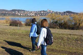 túrázók a Belső-tó mellett, háttérben az apátság