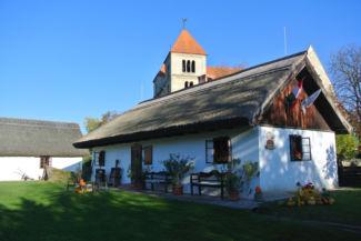a tájház egyik épülete, háttérben az egykori premontrei kolostorral