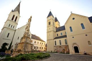 Szentháromság-szobor, háttérben balra a Szent István király-templommal, jobbra a Szent Mihály székesegyházzal