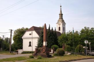 református templom, előtérben az I. világháborús emlékművel