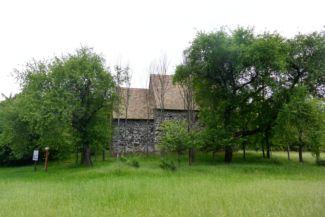alig látható az Apáti templomrom a fák között
