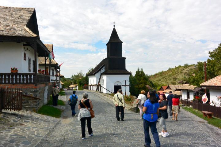 turisták a hollókői Ófaluban, a Szent Márton-templom mellett