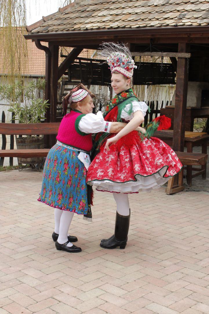 hollókői népviseletbe öltöztetnek egy lányt
