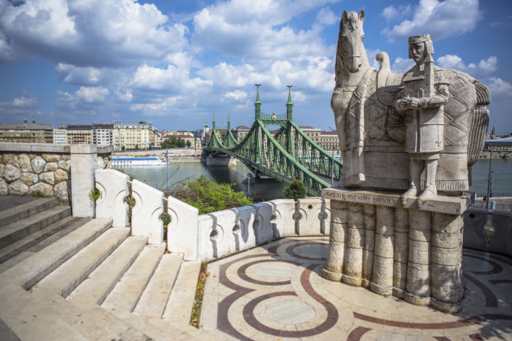 Szent István-szobor a sziklatemplom bejáratával szemben, háttérben Pest és a Szabadság híd