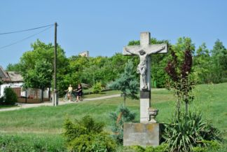 wayside cross with the medieval church ruins in the back