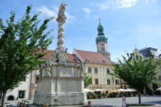 Szentháromság-szobor, háttérben a Storno-házzal és a Tűztoronnyal