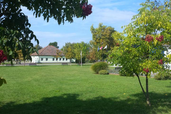 szépen gondozott park Apaj polgármesteri hivatala mellett, háttérben az iskola épületével