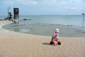 kislány motorozik rossz időben a Balaton partján