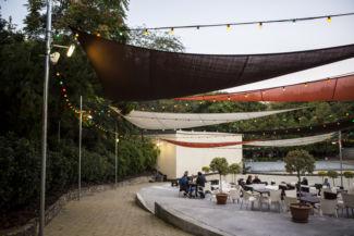 esővédők és színes izzósorok húzódnak az Új Budai Parkszínpad asztalai fölött