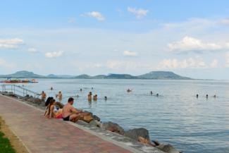 a balatongyöröki strand, háttérben a Balaton-felvidéki tanúhegyek